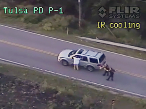 In this photo made from a Sept. 16, 2016 police video, Terence Crutcher, left, with his arms up is pursued by police officers as he walks next to his stalled SUV moments before he was shot and killed by one of the officers in Tulsa, Okla.