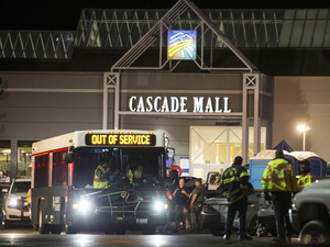 Emergency personnel stand in front of an entrance to the Cascade Mall at the scene of a shooting where five people were killed on Friday in Burlington, Wash.