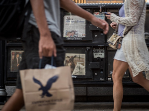 Pedestrians pass copies of newspapers for sale in Chicago, Ill., on Aug. 7, 2015.