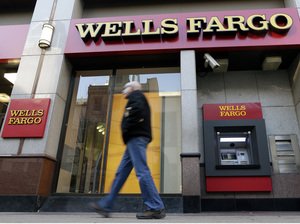 A man walks past a Wells Fargo branch in Philadelphia. The banking company says it wants to make good by its customers, but figuring out how to do that will be a tall task.