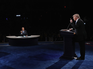 Republican presidential nominee Donald Trump speaks as Democratic presidential nominee Hillary Clinton and Moderator Lester Holt listen during the presidential debate at Hofstra University on September 26, 2016 in Hempstead, New York.
