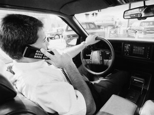 "The original caption to this 1989 photo read: ""Cellular phones are being offered by many car manufacturers as optional equipment for drivers who can't bear to be out of touch, even on the road."""
