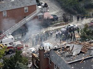 Emergency service personnel work at the scene of a house explosion in the Bronx on Tuesday.