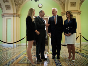 Sens. Chuck Schumer, D-N.Y., and John Cornyn, R-Texas, speak with Kaitlyn, left, and Terry Strada — whose husband, Thomas, died in the Sept. 11 attacks — after a May 17 news conference concerning the Justice Against Sponsors of Terrorism Act in Washington.