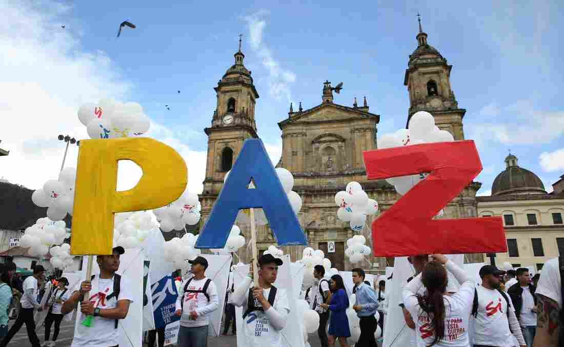 "Colombians in the capital, Bogota, hold up the letters for ""peace"" in Spanish on Monday. The Colombian government and FARC rebels signed a peace agreement, marking an end to the last war in the Western Hemisphere. Colombia's civil war lasted more than 50 years and Latin America has had civil wars for the past six decades. photo: Jennifer Alarcon/AP"