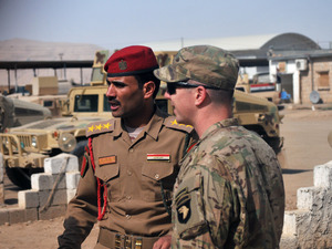 U.S. Army Capt. Gerrard Spinney (right) speaks to his Iraqi army counterpart from the Ninawa Operations Command prior to a security meeting at Camp Swift, Iraq, earlier this month.