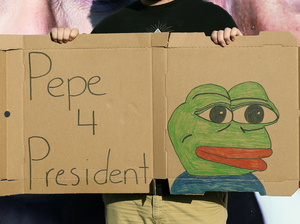 A man poses with a sign of Pepe the Frog outside Hofstra University in Hempstead, N.Y., site of Monday's first presidential debate between Donald Trump and Hillary Clinton.