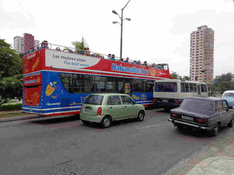 Tour buses full of tourists are now part of the flow of traffic in Havana.