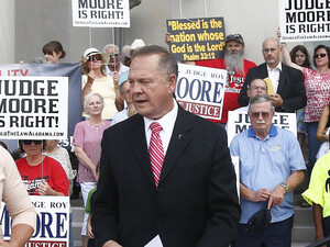 Alabama Chief Justice Roy Moore, seen here addressing the media in August, won't be paid for the rest of his term and must pay court costs.