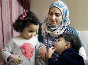 Syrian refugee Maryam al-Jaddou (center) sits with her children Maria (left) and Hasan at their apartment in Dallas. Jaddou says she decided to leave Syria in 2012 after her family's home in Homs was bombed and there was nowhere safe left to live.