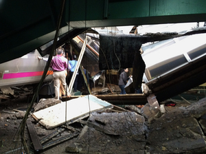 People examine the wreckage of a New Jersey Transit commuter train that crashed into the station in Hoboken,, N.J., during the morning rush hour Thursday.