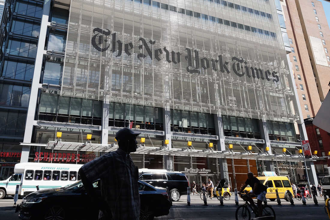Pedestrians walk by the outside of The New York Times Building in June.