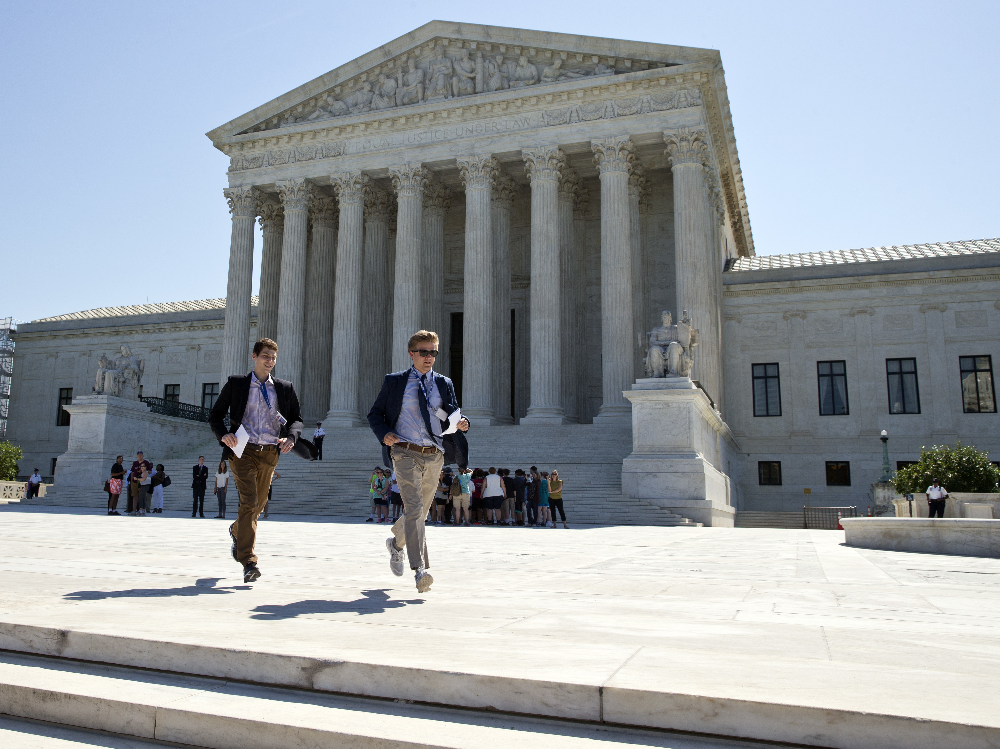In this June 20, 2016, file photo, runners leave the Supreme Court in Washington with papers announcing court decisions. The Supreme Court begins its new term Wednesday as it ended the last one--down one justice and ideologically deadlocked on a range of issues. Alex Brandon/AP.