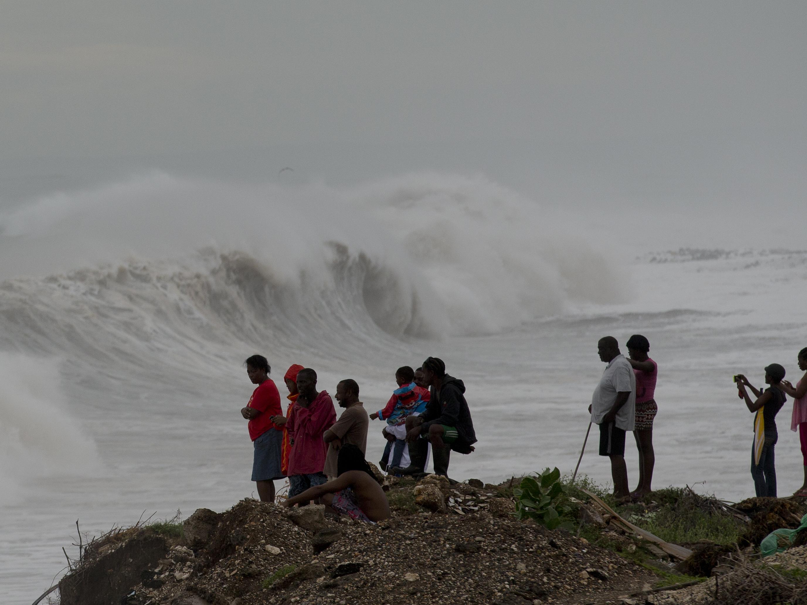 People watch waves break on the outskirts of Kingston, Jamaica, on Monday. Hurricane Matthew has generated large surf, heavy rain and wind. Eduardo Verdugo/AP.