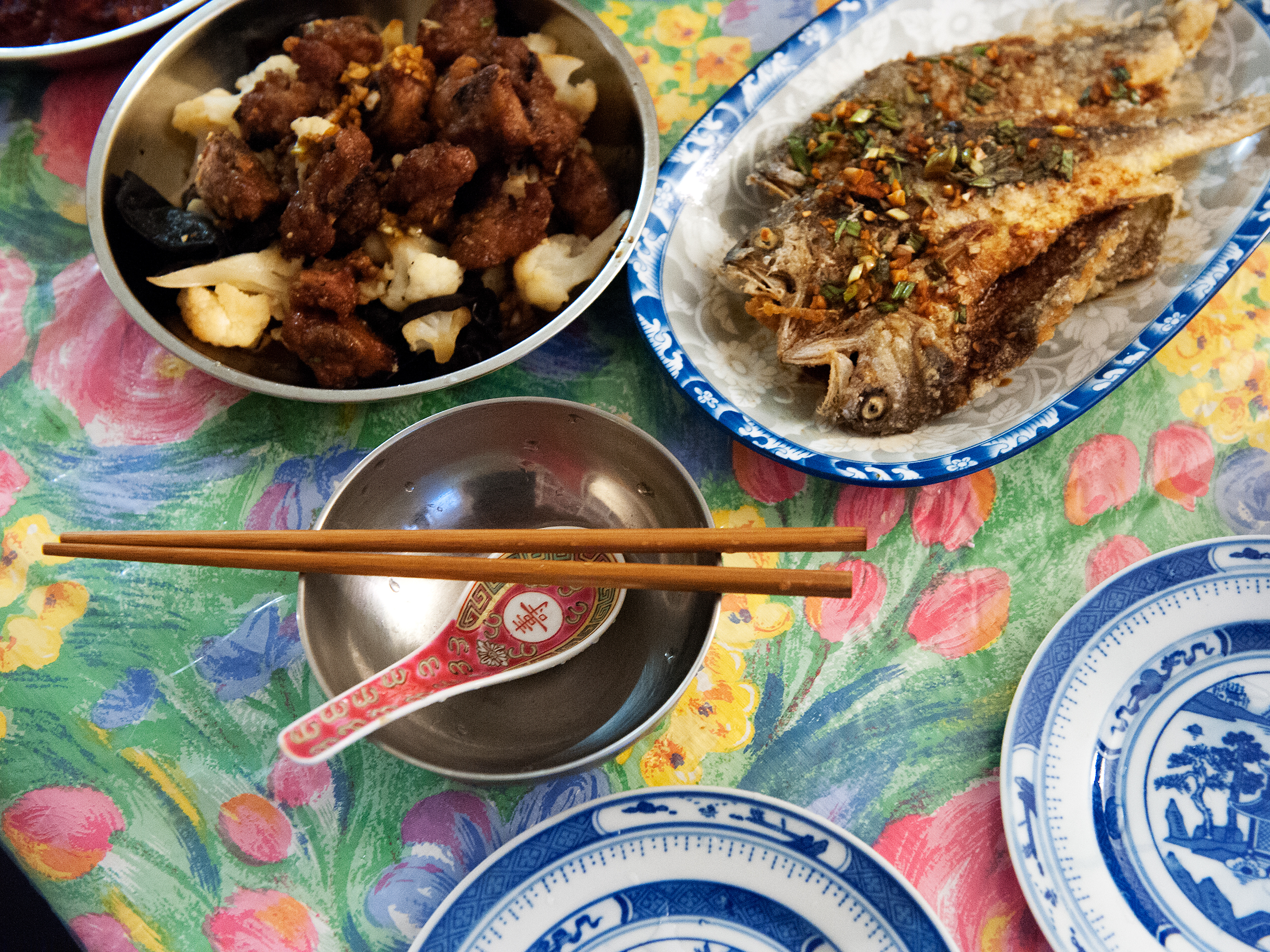 Plates of drunken pork ribs and deep-fried yellow croaker with savory soy sauce fill the dining table of Ni's home in New York City. Bryan Thomas for NPR