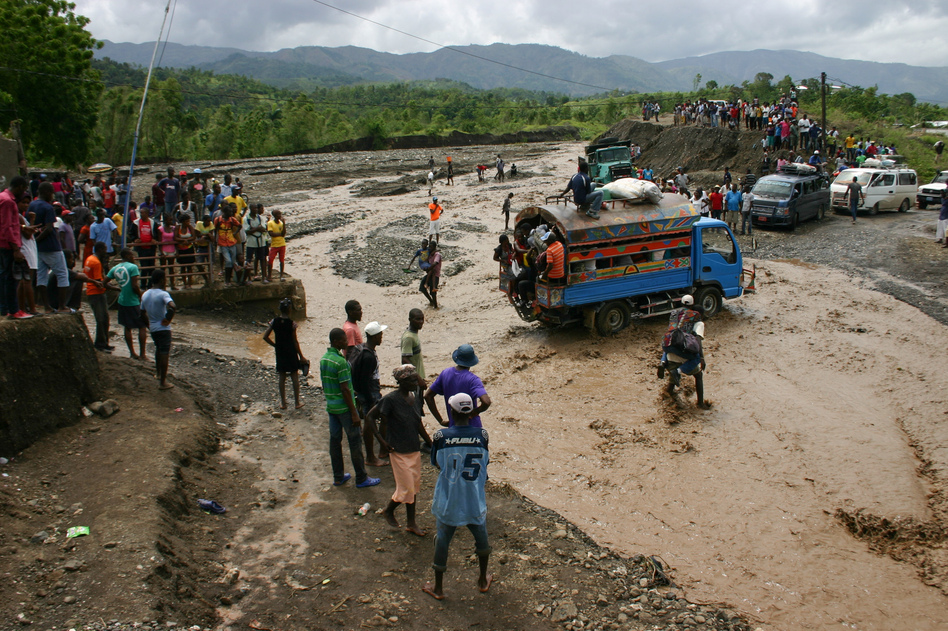 Haitians watch as people cross a river on National Route 2. Hurricane Matthew washed out a bridge at this spot cuttting off much of the southwest of the country from the capital Port au Prince. (Jason Beaubien/NPR)