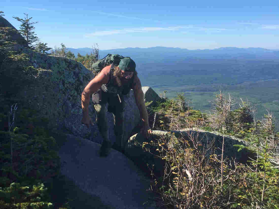 Marine Corps vet Daniel Dean climbs over a pink granite boulder on his way up Mount Katahdin. The trail stretches from Georgia to Maine, and usually takes about six months to complete.