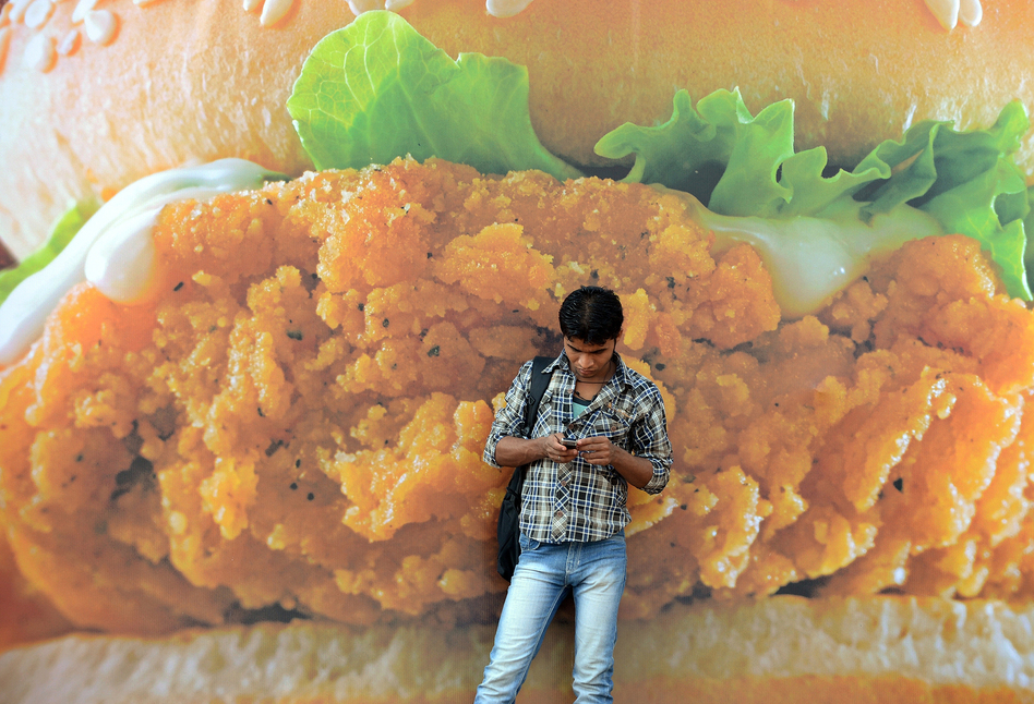 An Indian pedestrian checks his mobile phone in front of an advertisement for a burger of a fast-food giant in Mumbai, India. Fast food and highly processed foods and sodas are increasingly becoming more popular around the world, one of the main reasons for increasing rates of overweight and obesity. (Indranil Mukherjee/AFP/Getty Images)