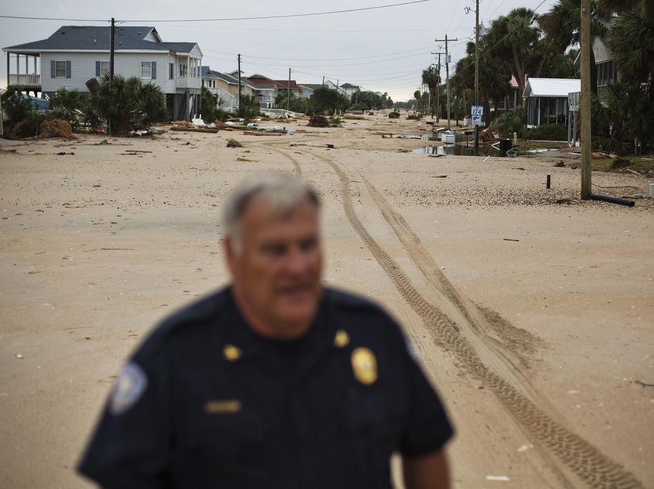 Chief of Police George Brothers walks along what used to be a four-lane national scenic byway that's now covered in sand after Hurricane Matthew hit the beach community of Edisto Beach, S.C., Saturday. (David Goldman/AP)