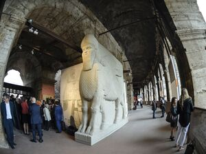 "People walk past a replica of an ancient statue of a human-headed winged bull from Nimrud, Iraq, destroyed by the Islamic State. It's part of an exhibition called ""Rising from Destruction"" at Rome's Colosseum."