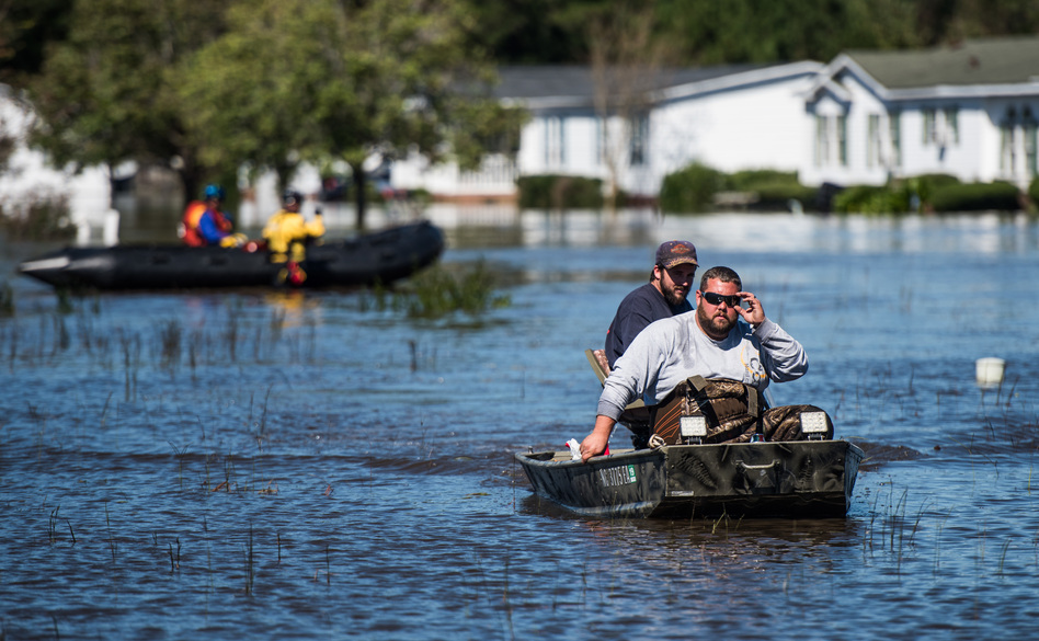 Residents and rescue teams navigate floodwaters in Lumberton on Monday. The U.S. death toll from Hurricane Matthew has climbed to more than 20 people. (Sean Rayford/Getty Images)