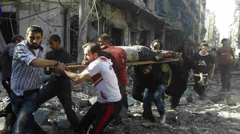 The Syrian volunteer rescue group, the White Helmets, carry a victim after airstrikes by government helicopters in a rebel-held part of Aleppo on Tuesday. The Syrian government and its Russian allies have been heavily bombing the rebel areas.