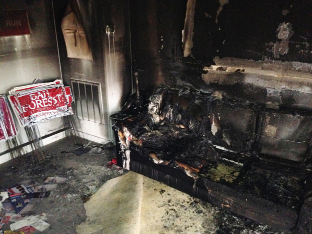 A burned couch rests next to warped campaign signs at the Orange County Republican Headquarters in Hillsborough, N.C.