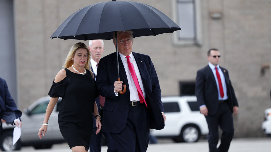 Republican nominee Donald Trump holds an umbrella while walking in the rain with Florida Attorney General Pam Bondi, as they arrive at a campaign rally in Tampa, Fla., in August.