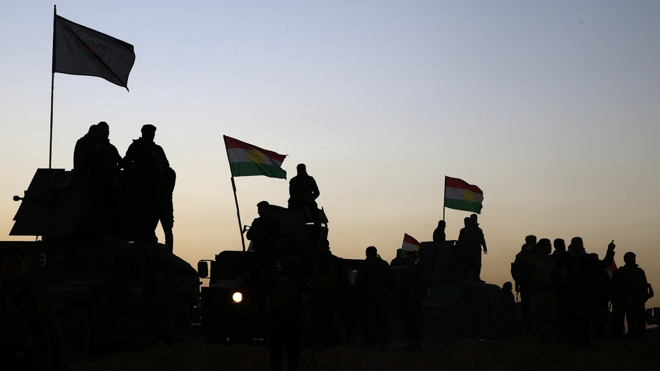 Kurdish peshmerga fighters, who are allied with the Iraqi army, stand atop military vehicles on Monday as they advance toward villages about 20 miles east of Mosul.The Iraqi military said an operation to retake Mosul from the Islamic State was launched before dawn on Monday.