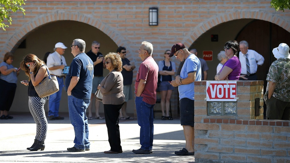 Voters wait in line to cast their ballot in Arizona's presidential primary election in Gilbert, Ariz., in March. (Matt York/AP)