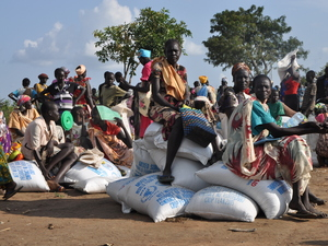 South Sudanese families sit with bags of food rations at the Ayilo Settlement Camp in northern Uganda. Refugees have been coming out of South Sudan in growing numbers since fighting resume there this summer.