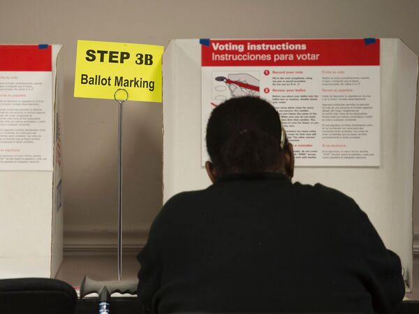 A voter casts a ballot at an absentee voting station in Fairfax, Va. Many polling places are preparing for the possibility of violence on Election Day.