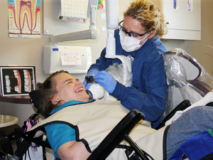 Hygienist Beth Rowan cleans the teeth of Lindsay Klecker, 31, who has cerebral palsy and a seizure disorder. Rowan works at the Marshfield Clinic in Chippewa Falls, Wis.