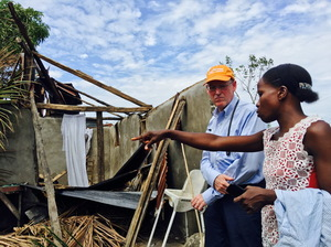 Dr. Paul Farmer, co-founder of Partners In Health, stands with Mirlande Estenale in front of what used to be her home in the town of Les Cayes, Haiti.