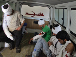Wounded rebel fighters sit in the back of an ambulance in Aleppo on Thursday. The Syrian government and their Russian allies declared a pause in the fighting and urged rebels to leave the eastern part of the city. But clashes broke out Thursday.