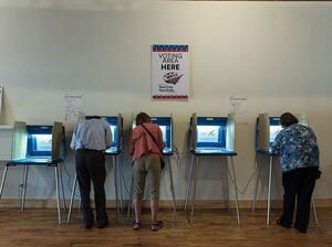 Three people vote in booths at the Early Vote Center in northeast Minneapolis, Minn., earlier this month.