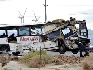 Workers prepare to haul away a tour bus that crashed with semi-truck on Interstate 10 near Palm Springs, Calif., Sunday. The crash killed at least a dozen people and injured at least 30 others, some critically, the California Highway Patrol said.