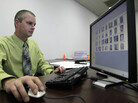 Stephen Lamm, a supervisor with the ID fraud unit of the North Carolina Department of Motor Vehicles, looks through photos in a facial recognition system in 2009 in Raleigh, N.C.