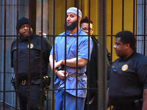 Officials escort Serial podcast subject Adnan Syed from the courthouse on Feb. 3 following the completion of the first day of hearings for a retrial in Baltimore. A judge granted the new trial — and now Syed has requested that he be released on bail while he waits for the retrial.