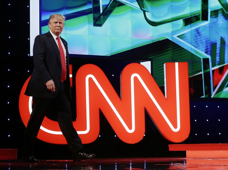 Donald Trump enters the debate hall during the Republican presidential debate co-sponsored by CNN in Coral Gables, Fla., in March. CNN is expected to see $100 million in extra revenues this year, thanks largely to its coverage of Trump. (Alan Diaz/AP)