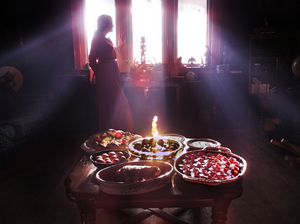 The bounty of the earth is celebrated in the high rituals of pagans. Above, a Wiccan priestess is silhouetted by the afternoon light. In the foreground are examples of Wiccan cooking for the vernal equinox. Clockwise from near right: beat-pickled eggs; roast beef in tarragon; bowl of eggs boiled with onion skin wrap; bread with eggs; Ukranian painted eggs; and apple crumble.