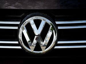 Volkswagen logos are visible at a dealership in Los Angeles on June 28. Volkswagen has agreed to pay out $14.7 billion in a settlement with U.S. authorities and car owners over its emissions-cheating diesel-powered cars. The settlement was approved on Tuesday.