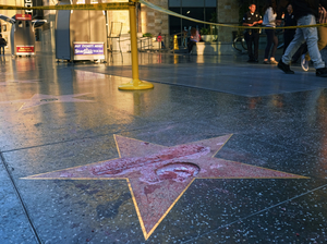 Pedestrians walk past a cordoned off area surrounding Donald Trump's vandalized star on the Hollywood Walk of Fame.