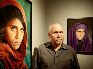 "Sharbat Gula, subject of the famous ""Afghan Girl"" image, is in a Pakistani jail over ID fraud. In 1984, Gula's brief encounter with photographer Steve McCurry, seen here next to images of Gula, led to a cover photo for National Geographic."