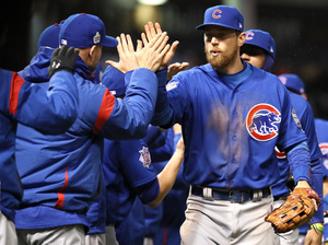 Ben Zobrist of the Chicago Cubs high-fives teammates after defeating the Cleveland Indians 5-1 in Game 2 of the World Series. The Cubs and Indians will face off in Chicago for Game 3.