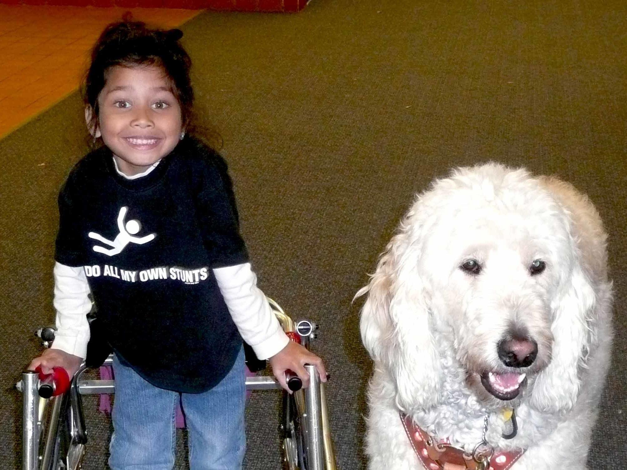Ehlena Fry, then in kindergarten, stands with her service dog, Wonder. Courtesy ACLU.