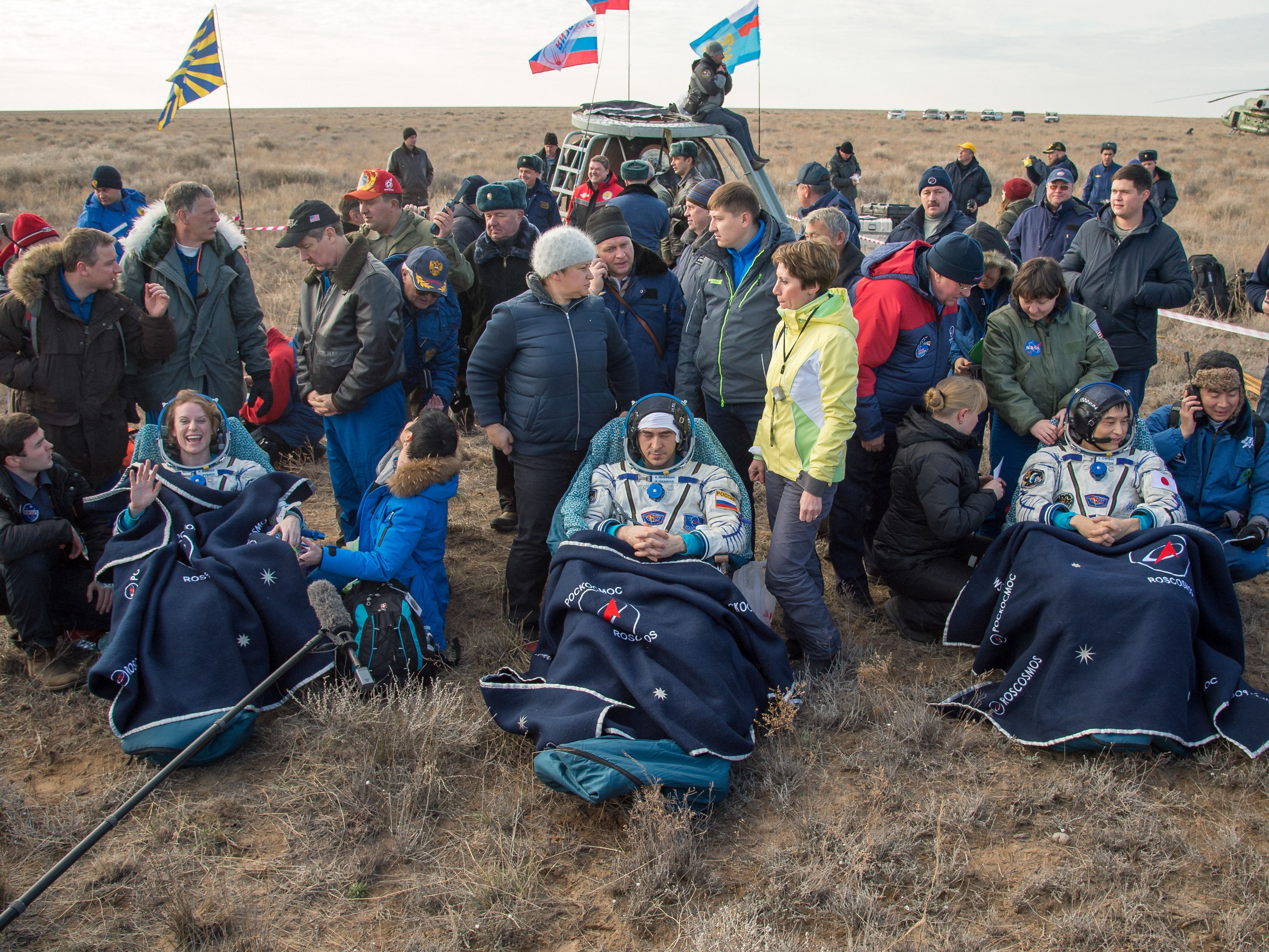 NASA astronaut Kate Rubins, left, Russian cosmonaut Anatoly Ivanishin of Roscosmos, center, and astronaut Takuya Onishi of the Japan Aerospace Exploration Agency sit outside the Soyuz MS-01 spacecraft a few minutes after they touched down on earth Sunday. Bill Ingalls/NASA.