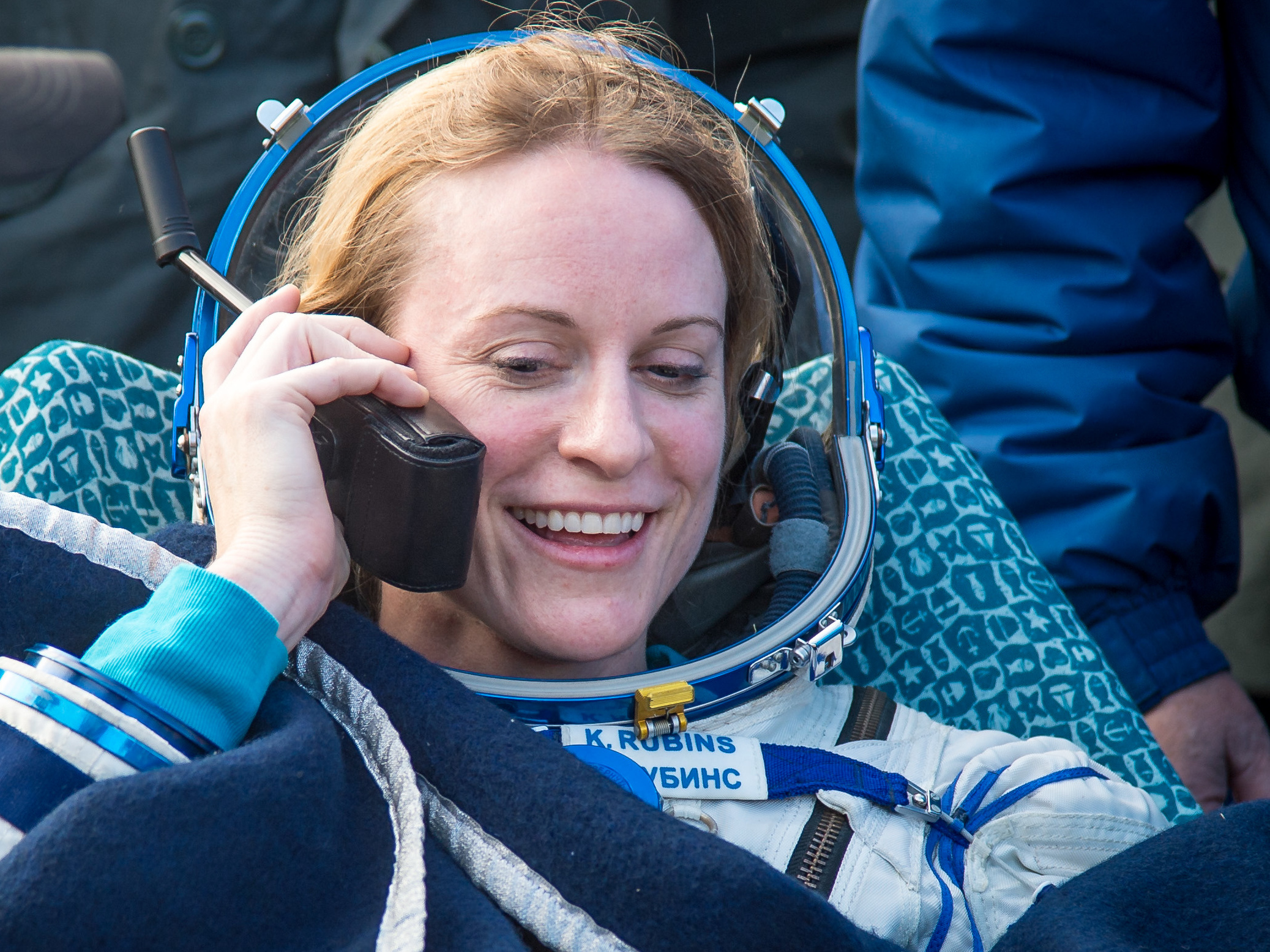 Astronaut Kate Rubins talks to her family via satellite phone shortly after she landed on earth after 115 days in space. Bill Ingalls/NASA.