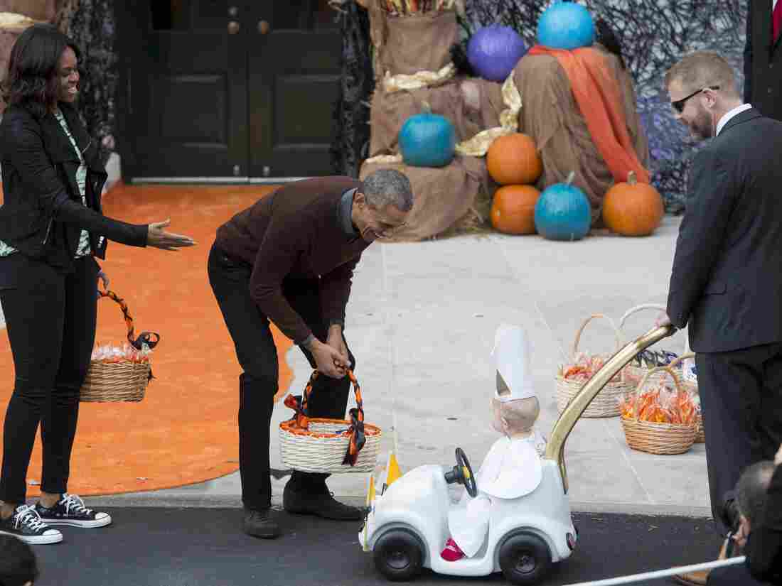 "President Obama greets a baby dressed as the Pope riding in a ""Popemobile."""