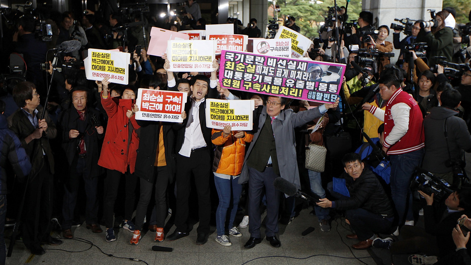 Anti-government protesters demonstrate as Choi Soon-sil, a confidante of South Korean President Park Geun-hye, appears at the Seoul Central Prosecutors' Office on Monday. (Woohae Cho/Getty Images)